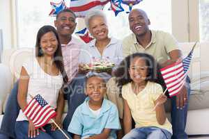 Family in living room on fourth of July with flags and cookies s
