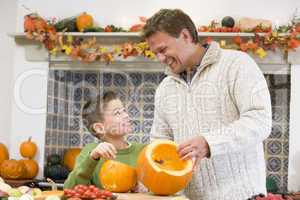 Father and son carving jack o lanterns on Halloween and smiling