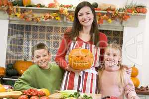 Mother and two children carving jack o lanterns on Halloween and