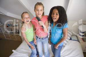 Three Young Girls Standing On A Bed, Singing Into A Hairbrush
