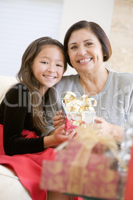 Grandmother And Granddaughter Sitting On Sofa Holding A Christma