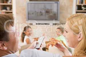 Couple Enjoying Pizza In Front Of TV