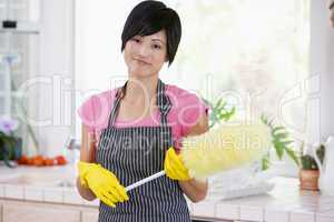 Woman Holding Duster And Wearing Rubber Gloves