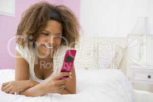 Teenage Girl Lying On Bed Using Cellphone