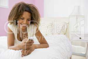 Teenage Girl Lying On Bed Using Mp3 Player