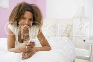 Teenage Girl Lying On Bed Using Mp3 Player