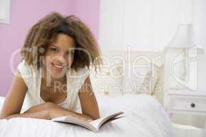 Teenage Girl Lying On Bed Reading