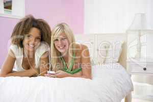 Teenage Girls Lying On Bed Listening To Mp3 Player