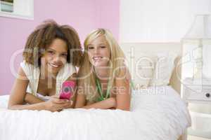 Teenage Girls Lying On Bed Using Cellphone