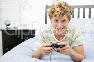 Teenage Boy Lying On Bed Playing Video Game