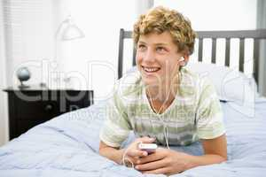 Teenage Boy Lying On Bed Listening To Mp3 Player