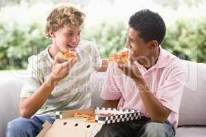 Zwei Jungen essen gemeinsam Pizza auf dem Sofa