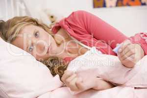 Teenage Girl Lying On Her Bed With A Pregnancy Test