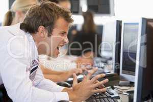 Ein Banker sitzt wütend vor seinem Computer