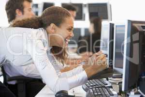 Junge Frau mit dunkler Haut jubelt vorm Bildschirm