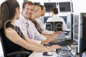 4 Kollegen sitzen nebeneinander am Bildschirm