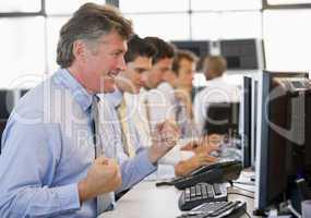 Ein älterer Herr jubelt vor seinem Bildschirm im Büro