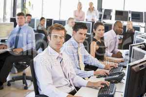 Verschiedene Menschen sitzen vor Bildschirmen