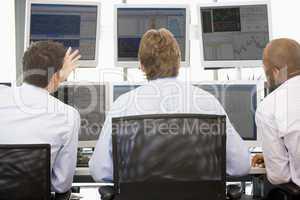 Drei Männer sitzen am Schreibtisch vor Bildschirmen