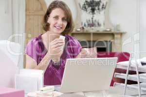 Junge Dame sitzt vor weißen Notebook