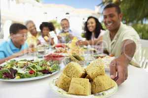 Große Familie sitzt an einem gedeckten Tisch