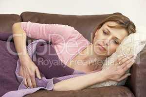 Woman Unwell And Lying On Sofa