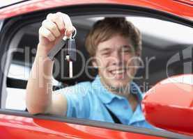 Junger Mann hält freudig den Autoschlüssel