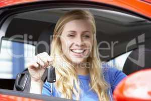 Junge Frau hält freudig den Autoschlüssel