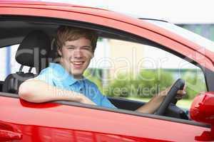 Junger Mann sitzt in einem roten Auto und lacht