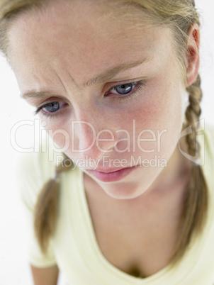 Mädchen mit rötlich-blonden Zöpfen kuckt traurig