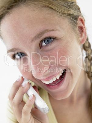 Mädchen mit rötlich-blonden Zöpfen hält ein Handy