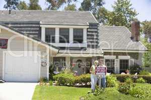 Ein Ehepaar steht vor einem verkäuflichen Haus