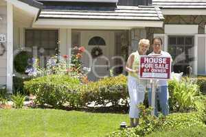 Ein Ehepaar vor einem verkäuflichen Haus