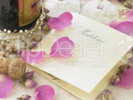 Wedding Invitation Next To Champagne Bottle Surrounded By Flower