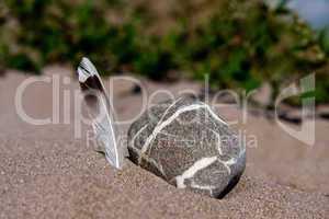 Steine und Feder im Sand