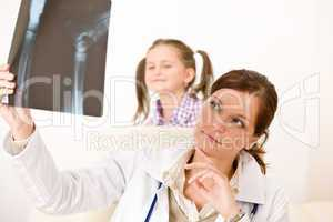 Young female doctor show x-ray to child