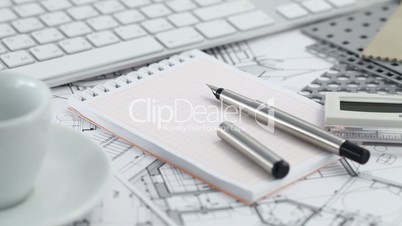 keyboard, cup, notepad, pen and architectural drawings