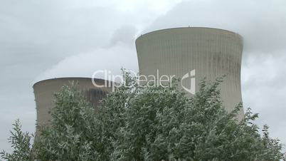 close shot of smoking chimneys of nuclear plant