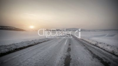 Driving in snow country with sunset in horizon