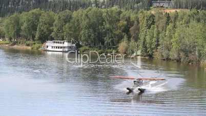 Float plane landing by river boat fairbanks P HD 1473