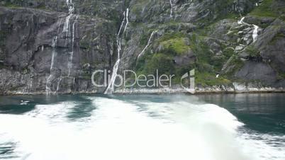 Boat leaving waterfalls fjord Alaska P HD 8379