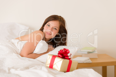 Bedroom surprise present - young happy woman