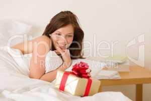 Bedroom surprise present - young happy woman