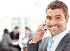 Handsome businessman on the phone in the foreground