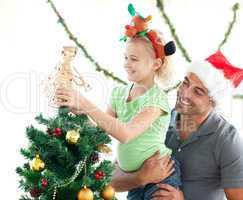 Cute little girl decorating the christmas tree with her father