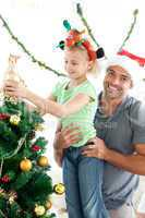 Happy father helping his daughter to put an angel on the Christm