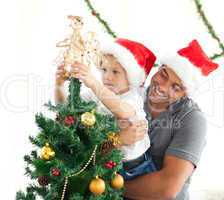 Happy father helping his son to put an angel on the Christmas tr