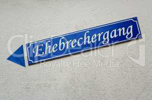 Straßenschild mit Name Ehebrechergang in blau