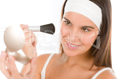 Skin care - young woman apply powder