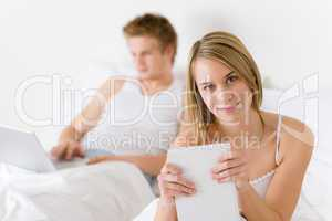 Bedroom - young couple with laptop and book